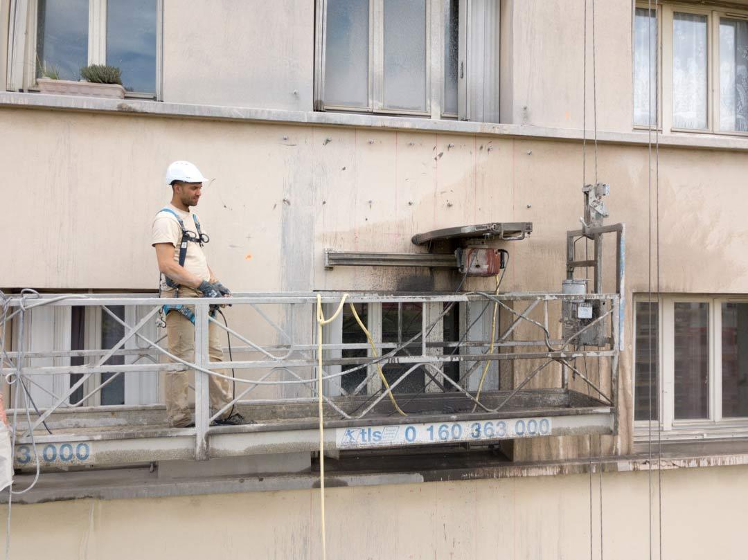 Scie télécommandée en cours de découpe d'une allège en béton
